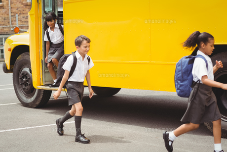 Cute schoolchildren getting off the school bus FYI00005511