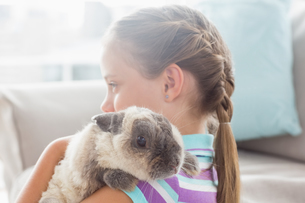 Girl holding rabbit at home FYI00005906