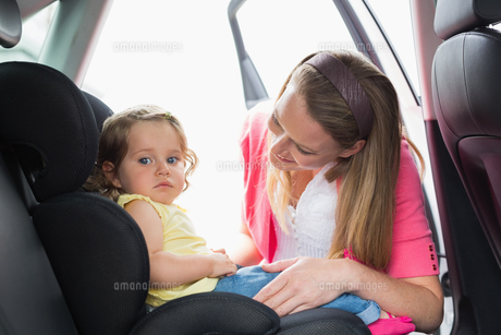 Mother securing her baby in the car seat FYI00005964