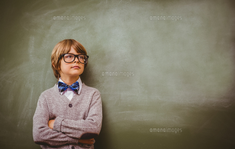 Boy with arms crossed looking up at blackboard FYI00006024