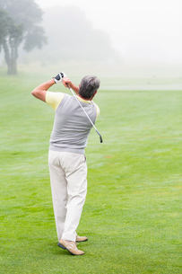 Golfer swinging his club on the course FYI00006037