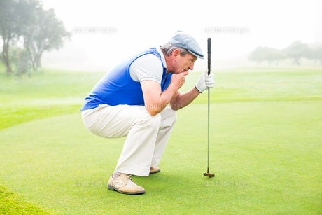 Serious golfer kneeling on the putting green FYI00006041