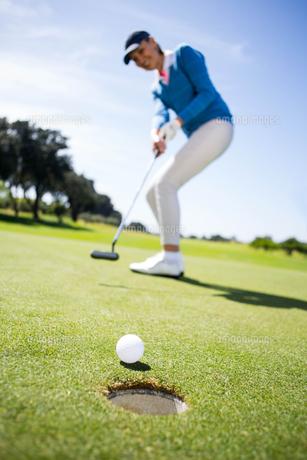 Female golfer putting her ball FYI00006052