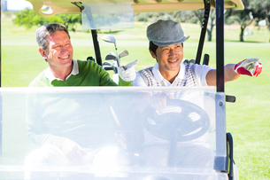 Golfing friends driving in their golf buggy FYI00006097
