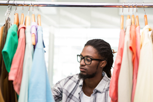 Male fashion designer looking at rack of clothes FYI00006123