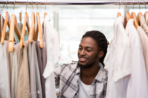 Male fashion designer looking at rack of clothes FYI00006127