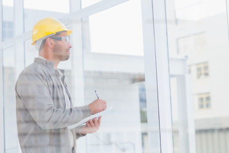 Architect writing on clipboard while looking through office window FYI00006190