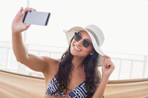 Pretty brunette relaxing on a hammock and taking selfie FYI00006307