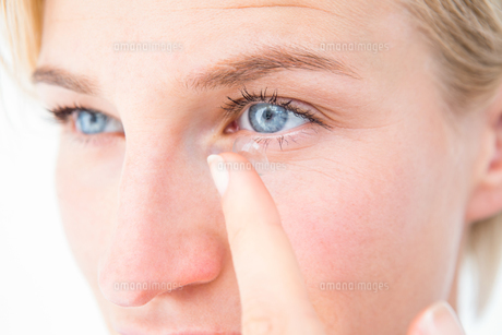 Pretty blonde applying contact lens FYI00006611