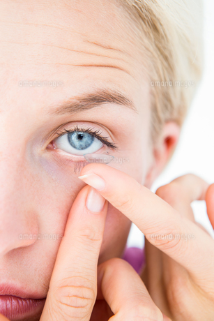 Pretty blonde applying contact lens FYI00006614