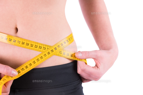 Slim woman measuring waist with tape measure FYI00006692