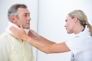 Doctor examining patient wearing neck brace FYI00006720