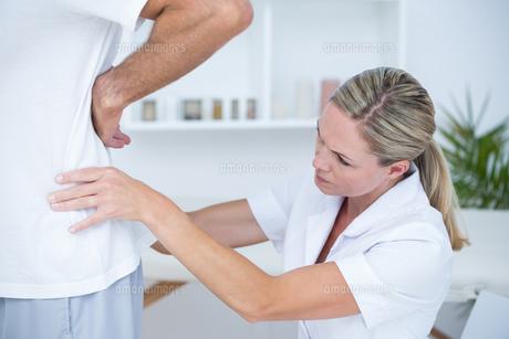 Doctor examining her patient back FYI00006733