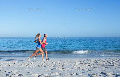 Happy couple running together beside the water FYI00006818