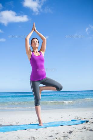 Brunette doing yoga on exercise mat FYI00006865