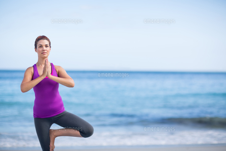 Brunette doing yoga on exercise mat FYI00006867