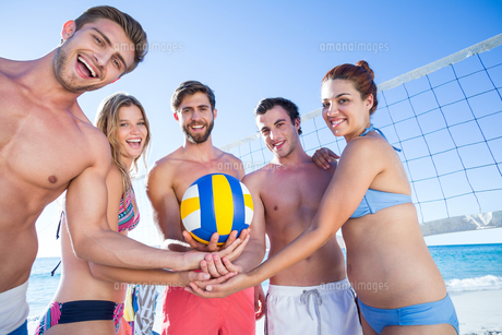 Group of friends holding volleyball and smiling at camera FYI00007030