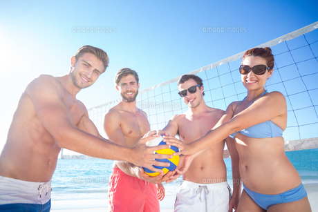 Group of friends holding volleyball and smiling at camera FYI00007036