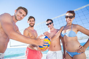 Group of friends holding volleyball and smiling at camera FYI00007038