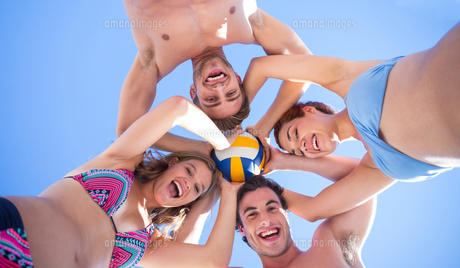 Group of friends standing in circle and holding ball FYI00007044