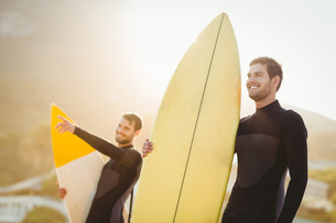 Two men in wetsuits with a surfboard on a sunny day FYI00007100