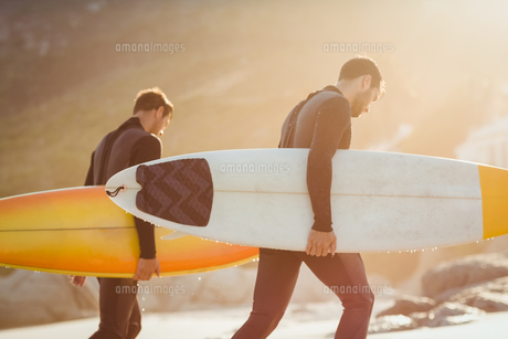 Two men in wetsuits with a surfboard on a sunny day FYI00007105