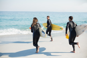 Group of friends on wetsuits with a surfboard on a sunny day FYI00007116
