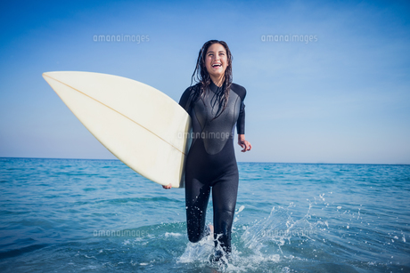 woman in wetsuit with a surfboard on a sunny day FYI00007121