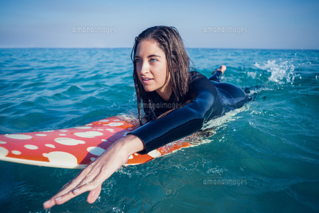 woman in wetsuit with a surfboard on a sunny day FYI00007125