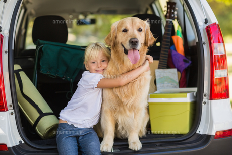 Smiling little girl with her dog in car trunk FYI00007289