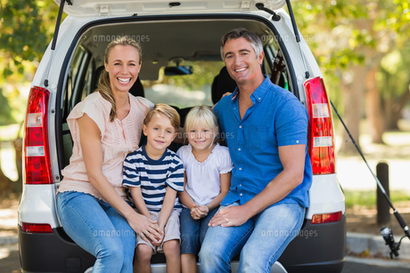 Happy family of four sitting in car trunk FYI00007302
