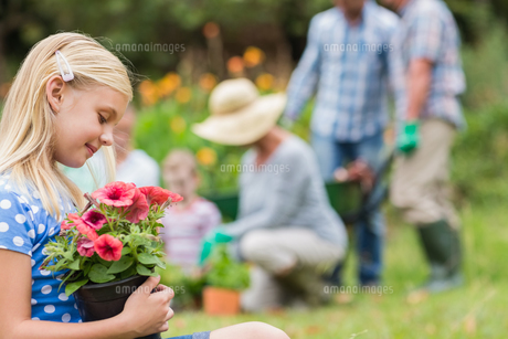 Young girl sitting with flower pot FYI00007391