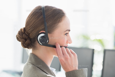 Smiling businesswoman with headset using computers FYI00007465