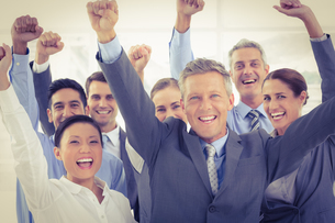 Business people cheering in office FYI00007646