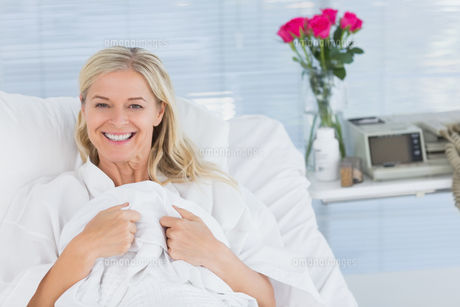 Smiling patient looking at camera on her bed FYI00007813