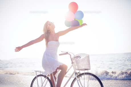 Beautiful blonde on bike ride holding balloons FYI00007874