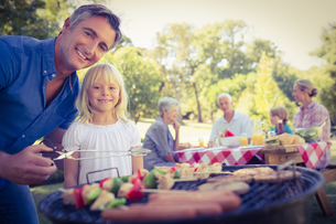 Happy father doing barbecue with her daughter FYI00007940