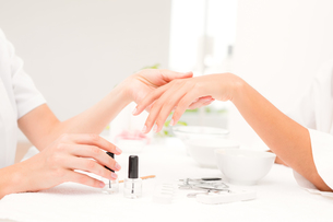Beautician filing female clients nails at spa beauty salon FYI00008216