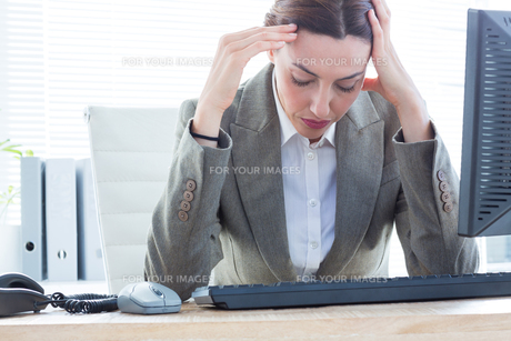 Upset business woman with head in hands in front of computer at office FYI00008277