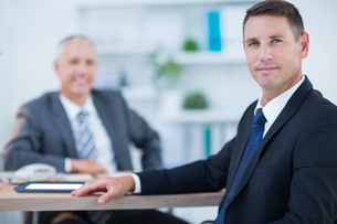 Confident businessman looking at camera with colleague behind FYI00008306