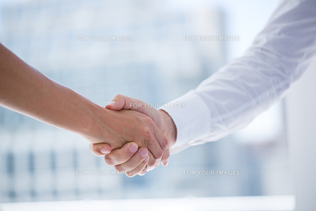 Close up view of two business people shaking hands FYI00008341