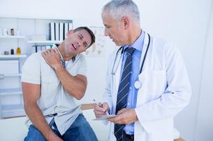 Doctor looking at patient shoulder FYI00008457