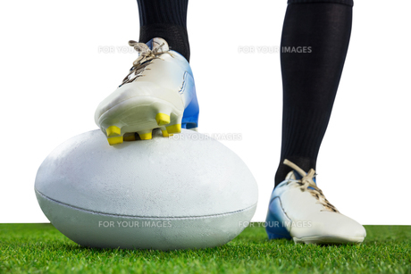 Rugby player posing feet on the ball FYI00008682