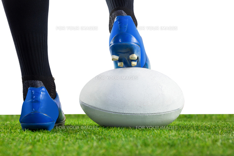 Rugby player posing feet on the ball FYI00008685
