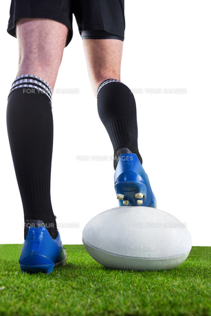 Rugby player posing feet on the ball FYI00008692