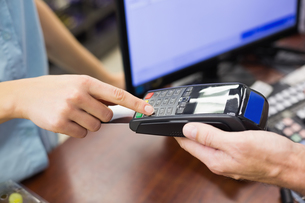 Woman at cash register paying with credit card FYI00008860