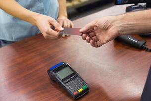 Woman at cash register paying with credit card FYI00008865