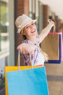 Carefree woman holding shopping bags FYI00008979