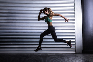 Muscular woman running in exercise room FYI00009062