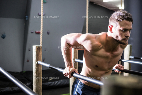 Muscular man exercising on parallel bars FYI00009219